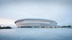 Die Aixer Arena – eine zurückhaltende, zugleich präsente Gebäudefigur, charakterisiert durch übereinander versetzt angeordnete, helle Bänder über einer transparenten Erdgeschosszone