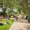 Gesamtansicht mit Wege und Rasenflächen, Lattenboden, Glaspavillion und Möblierung