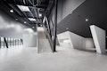 1.Die gebäudehohen, in Beton und Schwarz gehaltenen Foyerbereiche führen direkt in die große Veranstaltungshalle, die den gleichen Farb- und Materialkanon aufweist