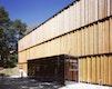 Holzfassade mit gläserner Eingangsbox