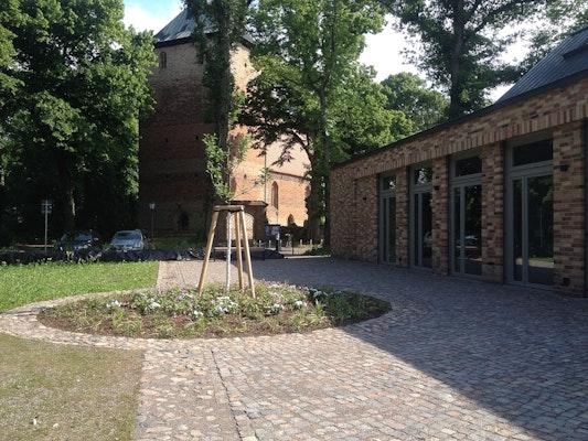 Pflasterwege und Pflanzinsel entlang des Gemeindehauses