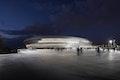 Die abends beleuchteten Untersichten der Bänder verschieben auch in der Lichtwirkung den Schwerpunkt der Arena in Richtung des Vorplatzes